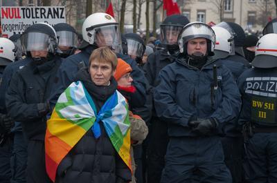 Frau protestiert mit Regenbogenfahne am 19.2. in Dresden , im Hintergrnd Polizisten in ener Reihe