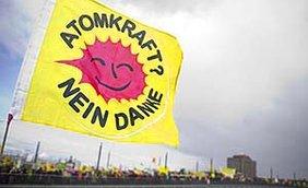 """""""Atomkraft - Nein, danke""""-Fahne, im Hintergrund ein Protestzug"""