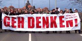 """Menschen demonstrieren im Zentrum Dresden mit dem Transparent """"Geh denken - Diese Stadt hat Nazis satt!"""""""
